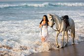 happy young woman walking with a white horse on beach