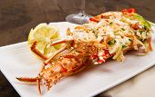 picture of lobster tail  - white dish with catalan lobster  on wood background - JPG