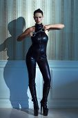 foto of catsuit  - Young beautiful woman in latex catsuit holding handcuffs desire - JPG