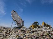 picture of landfill  - Modern hydraulic disposer empties a complete trailer while bulldozer manages landfill - JPG