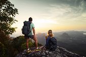Two hikers relaxing on top of hill and enjoying sunrise over the valley