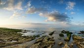 Panorama Landscape Looking Out To Sea With Rocky Coastline And Beautful Vibrant Sky