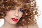 Close-up portrait of young beautiful woman with curly hair and red lipstick, selective focus