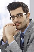 Closeup portrait of handsome young businessman in glasses, thinking, looking at camera.