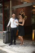 Young couple standing at doorway of hotel waiting for taxi with suitcase.