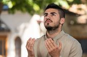 stock photo of prayer  - Young Muslim Man Making Traditional Prayer To God While Wearing A Traditional Cap Dishdasha - JPG