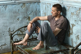 picture of scourge  - Man on the metal rusty bed in prison - JPG