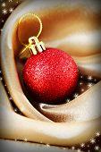 Beautiful Christmas ball on golden satin cloth