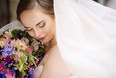 foto of bridal veil  - Beautiful bride in veil standing by the old stone chapel - JPG