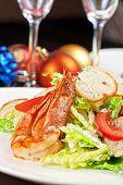 Tasty shrimp salad with vegetables on christmas table