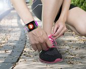 Human Hand Tying Shoelaces Wearing Bright Pink Watchband Touchscreen Smartwatch