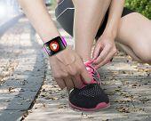 Human Hand Tying Shoelaces Wearing Bright Pink Watchband Touchscreen Smartwatch