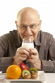 stock photo of senior men  - Senior man having a healthy breakfast isolated on white - JPG