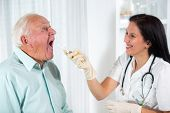Doctor looks in the throat an older man