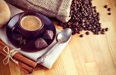 Cup hot coffee with beans and chocolate candies instagram styled vintage retro photo