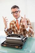 Happy vintage man with glasses gesturing in his office