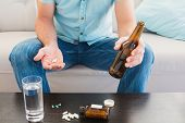 Man with a beer and his medicine laid out on coffee table