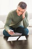 Smiling man using mobile phone near ripped paper at home in the living room