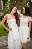 Pretty friends smiling in white dresses outside in the garden