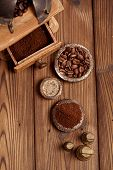 grated coffee in old iron weights and wooden  background