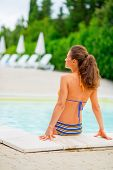 Young Woman Sitting At Poolside. Rear View