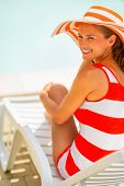 Smiling Young Woman In Hat Sitting On Sunbed