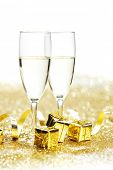 Champagne glasses and gifts on glitters with white copy space
