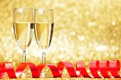 Two glasses of champagne with red bow on golden background