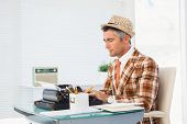 Retro man in straw hat typing on typewriter in his office
