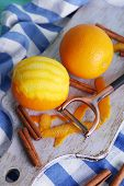picture of orange peel  - Ripe and peeled oranges and peeling knife on cutting board on fabric background - JPG