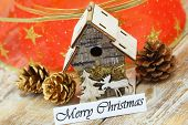 Merry Christmas card with miniature bird feeder, pine cones and red ribbon