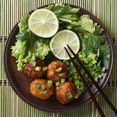 Fish Balls With Lime And Fresh Herbs On A Bamboo Table Top View