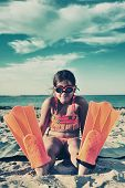 picture of flipper  - Young girl with flippers standing on beach - JPG