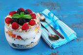 Healthy breakfast - yogurt with  fresh fruit, berries and muesli served in glass jar, on color wooden background