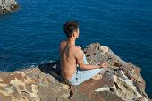 Handsome man in a yoga position sitting on the beach
