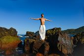 Full body Asian man standing, in yoga pose, on the beach
