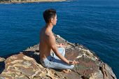 Young man meditating sitting on a rock. Soft Focus on man