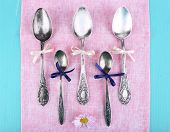 Metal spoons on pink napkin on light blue wooden background