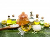 spa supplies with orchid, oil, yellow candle ,soap ,salt ,oil on banana leaf