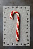 Closeup high angle shot of an old fashioned candy cane on parchment paper with star shapes cut into the papers edge. Vertical format.