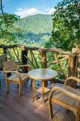 Wooden table and chairs in the cafe with a wonderful mountain view. Northern Thailand.