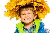 Little happy boy in maple wreath on white