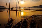 Silhouette of fisherman and traditional thai boats at Sam chong Tai Phangnga province.
