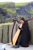 Woman playing the harp for tourists. Cliffs of Moher