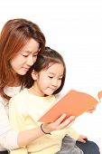 Japanese mother reading a book to her daughter