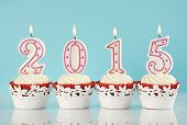 Happy New Year For 2015 Red Velvet Cupcakes In Red And White Theme With Lit Candles And Pale Blue An