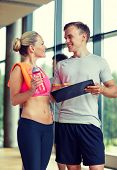 fitness, sport, exercising and diet concept - smiling young woman with personal trainer after training in gym