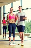 sport, fitness, lifestyle and people concept - smiling man and woman with scales and clipboard showing thumbs up in gym