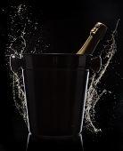 Champagne bucket on black background, celebration theme.