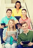 education and technology concept - smiling students with tablet pc computer sitting on staircase